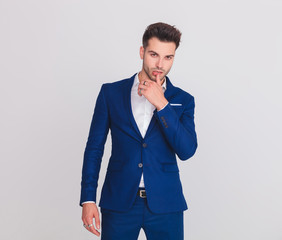 portrait of seductive man in blue suit touching his lips