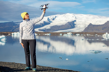 young woman launches quadcopter. Woman with gadget on a background of beautiful blue mountains and ice