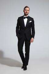 arrogant elegant man in tuxedo standing with hand in pocket
