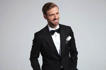 cool elegant man in tuxedo is laughing while looking away