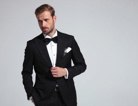 sexy elegant man wearing tuxedo and bowtie posing