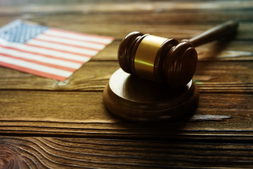 Judge's gavel, flag of the United States of America against the background of a wooden table. jurisprudence, legislation.