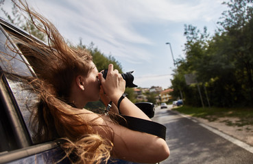 Young white girl taking pictures from the car window. Montenegro.