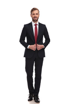 young smiling businessman buttoning his suit while standing