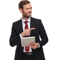 curious businessman with tablet looks and points to side