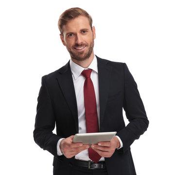 portrait of smiling unshaved businessman holing a tablet