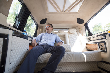 Businessman relaxing in back seat of moving car.