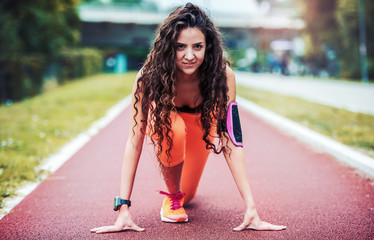 Athlete woman in starting run position. Sport, fitness, athletics concept
