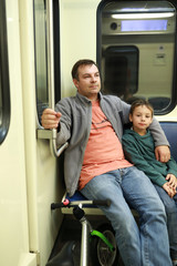 Father and son in subway train