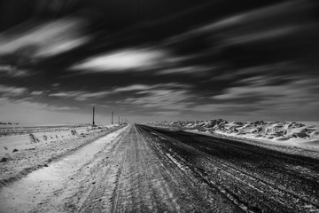 Empty freeway at night. Black and white. Road to the horizon. Clouds, rapidly running across the sky.