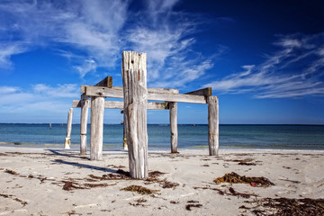 Old ruinous jetty with wooden timber at a sunny morning light at a deserted beach as wide-angle panorama
