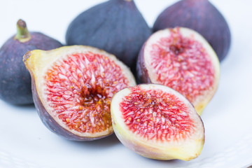 Fresh figs. Vegetarian Food. Whole and sliced figs on a white plate on white background. Copy space. Close up.