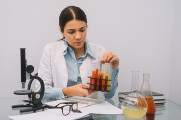 Beautiful medical doctors in gloves and glasses are working with substances in test tubes and microscope at the lab. Photo of attractive concentrated female doctor writing prescription on special form