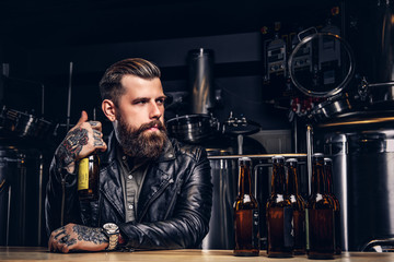 Stylish bearded biker dressed black leather jacket sitting at bar counter in indie brewery. Wall mural