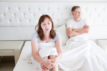 Family life concept.Problems in relationships. Middle age couple in bedroom. Man and woman in bed. Quarrel and upset emotions. Selective focus
