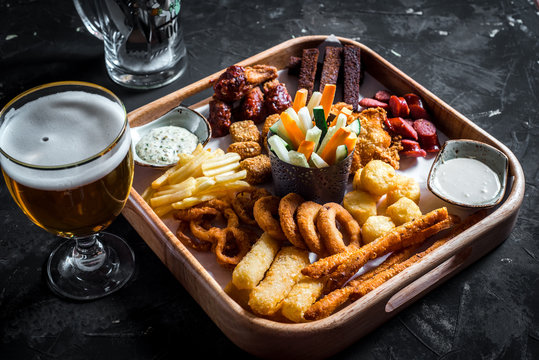 Set of assorted beer snacks - sausages, chicken wings, croutons, onion rings and squid rings on wooden board with sauce and glass of beer