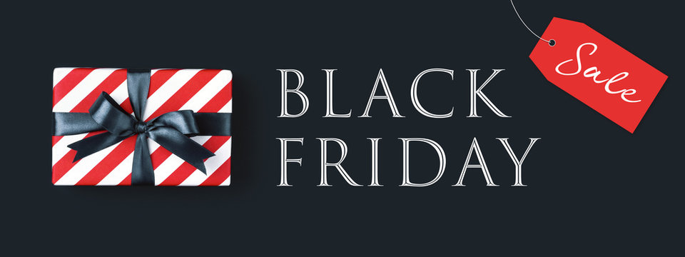 Black friday banner with gift box wrapped in red striped paper and tied with black bow on black background, top view.