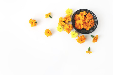 Dia de los Muertos, Mexican Day of the Dead desk composition. Orange tagetes, marigold and yellow chrysanthemum flowers in black bowl and on white table background. Halloween flat lay, top view