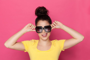 Grimacing Woman In Big Sunglasses In Sticking Out Tongue