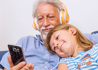 grandfather and grandson listen music on the couch