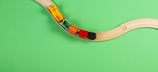 Toy train and wooden rails on green background