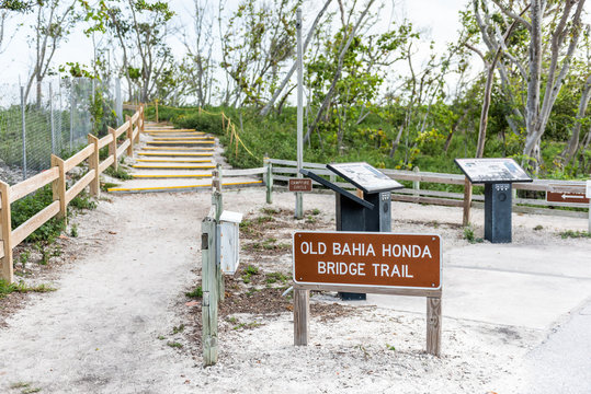 Sign for Old Bahia Honda Bridge Trail in state park during day sunset evening in Florida Keys, with hiking path