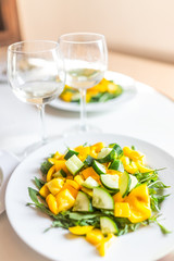 Closeup of fresh arugula yellow bell pepper salad on light sunlight table in Italy with white wine, vegetables, two romantic lunch or dinner glasses in restaurant