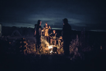 Group of men people travelers tourist resting camp fire in outdoors camp after long hunting day in the night    Wall mural