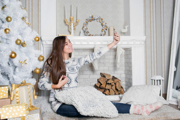 Young attractive brunette woman near the fireplace, cosiness home interior. Teenage girl in white sweater makes selfie. Winter holidays concept. White beautiful decor. Sincere smile. Christmas tree.
