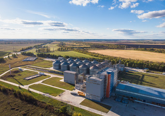 Large modern silos granary steel tanks or containers for silos, wheat and other cereals. Industrial agriculture and farming, aerial view