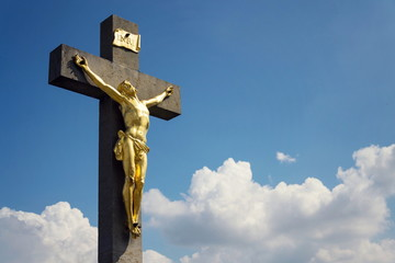 Golden Jesus Christ crucifixion statue, sunny summer day blue sky background, Vrbice, Moravia, Czech Republic