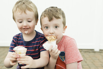 Brothers eating ice cream cones while sitting against wall
