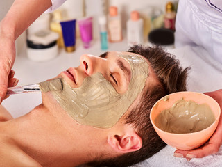 Mud facial mask of man in spa salon. Cleansing massage with clay full face. Lying man on therapy room for skin detox. Beautician with bowl therapeutic procedure. Anti-aging cosmetic mask.