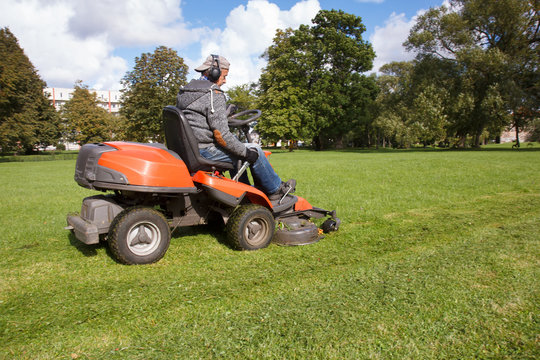 lawn mower tractor working in the town park