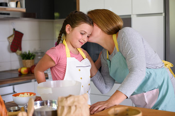 Mother kissing a her daughter that helps in the kitchen