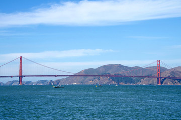 Golden Gate Bridge, viewed Little Marina Green, blue cloudy sky and Marin hills in background