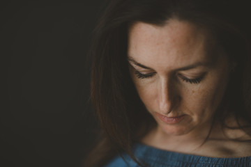 Close-up of thoughtful woman looking down against black background