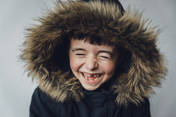 Close-up of happy boy in fur coat standing against white background