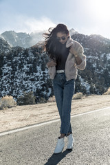 Full length of fashionable young woman standing on road against mountains during sunny day