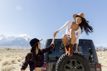 Smiling young woman helping friend to jump from off-road vehicle's spare tire at desert during sunny day