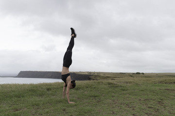 Side view of woman doing handstand on field against cloudy sky Wall mural
