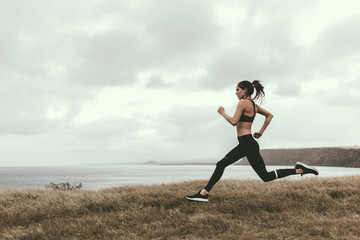 Woman running on grassy field by sea against cloudy sky