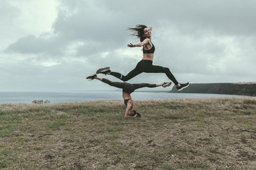 Female friends exercising on grassy field by sea against cloudy sky