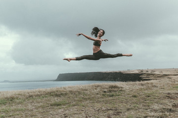 Woman jumping over grassy field by sea against cloudy sky