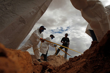 Forensic workers bury an unclaimed body in a mass grave at San Rafael cemetery in Ciudad Juarez