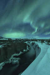 Scenic view of river amidst glaciers against aurora borealis at night