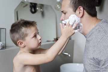 Shirtless son applying shaving cream on father's beard in bathroom