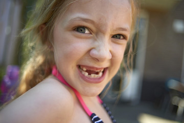 Close-up portrait of girl with gap toothed making face at backyard
