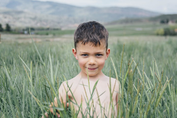 Portrait of shirtless boy standing amidst plants against mountain