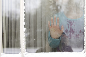 Midsection of girl in house seen through window during winter